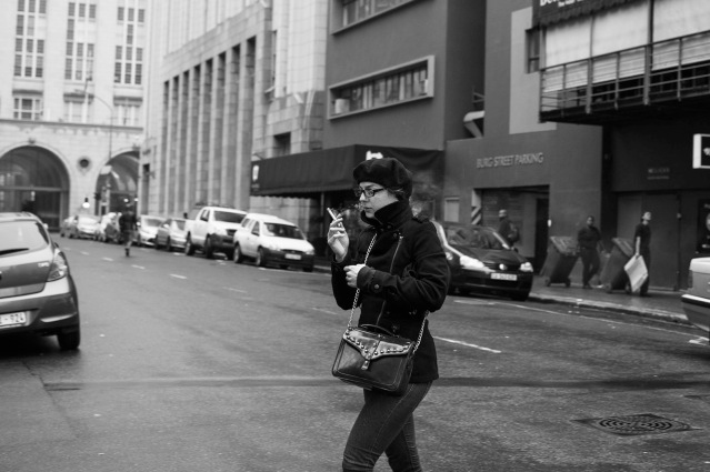 Woman crossing street smoking